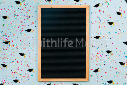 Letterboard Surrounded by Confetti and Graduation Caps