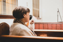 Woman Sitting in Pew and Taking a Sip of Coffee  image 2