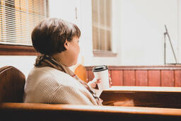 Woman Sitting in Pew and Taking a Sip of Coffee  image 3