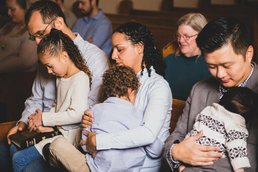 Young Family Praying Together at Church