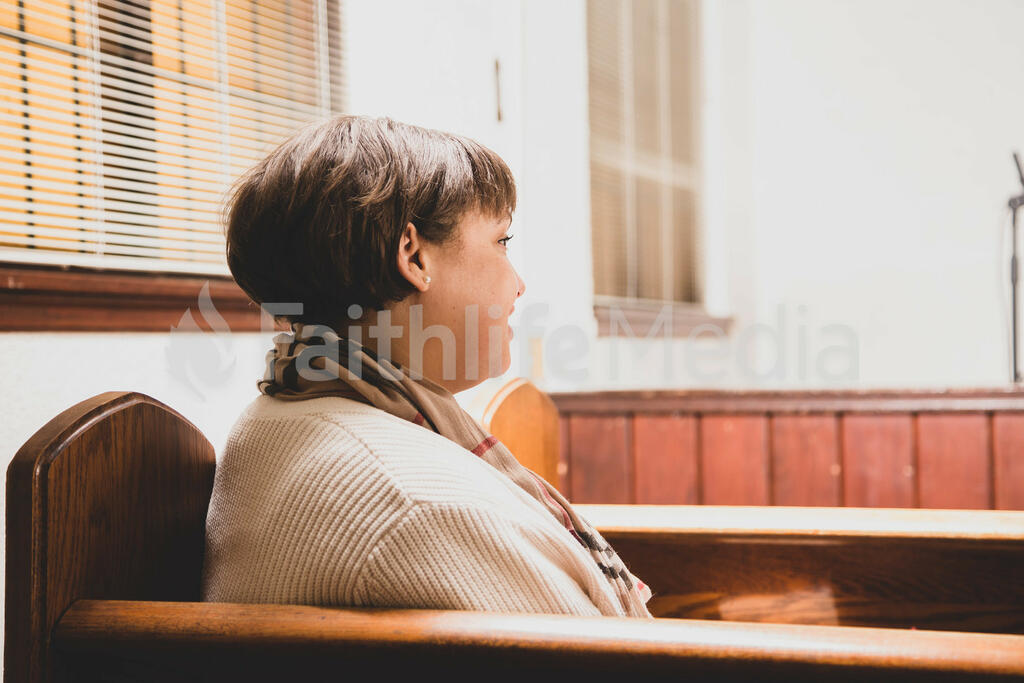 Woman Sitting in Pew and Taking a Sip of Coffee large preview