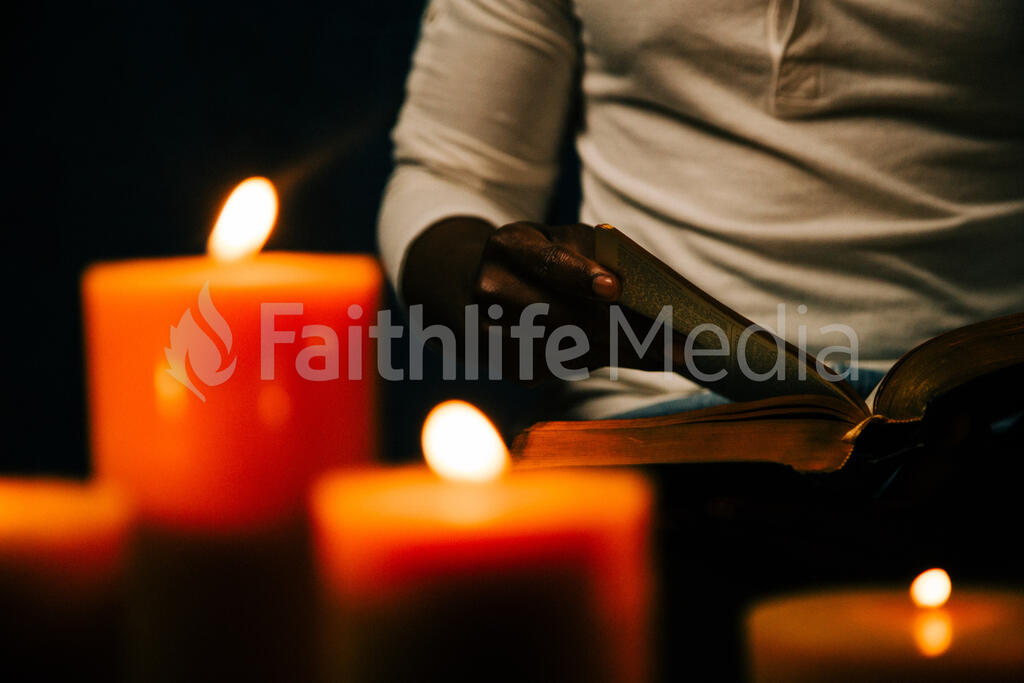 Man Reading Bible in Candle Lit Room large preview