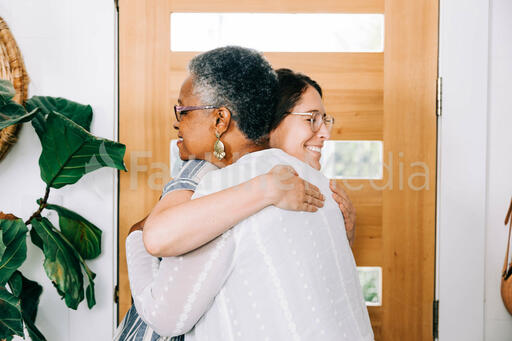 Women Hugging at Entrance of Home before Small Group