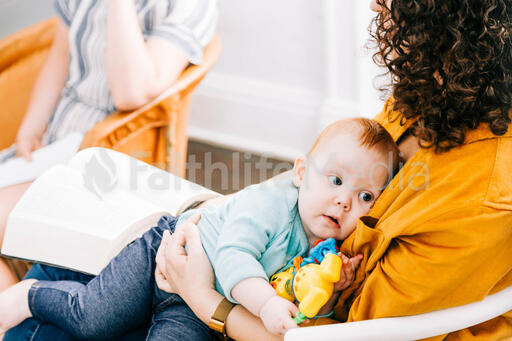 Woman Holding Baby and Open Bible