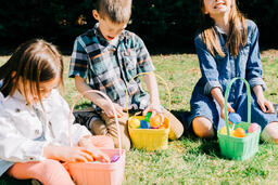 Kids Laughing and Looking Through Their Easter Eggs Together  image 2