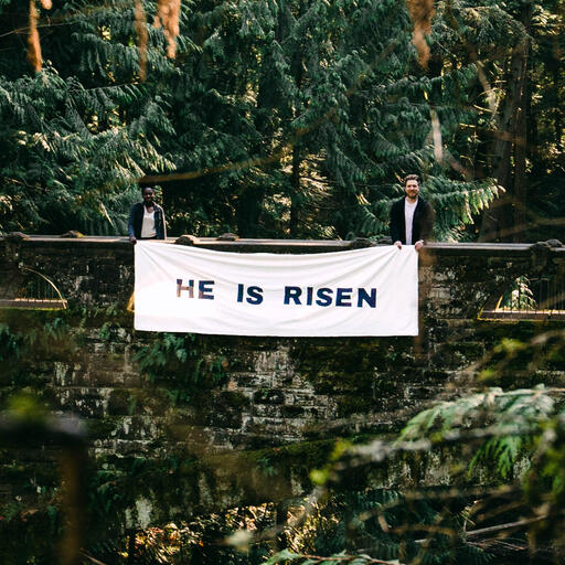 People Holding a He Is Risen Banner in the Forest