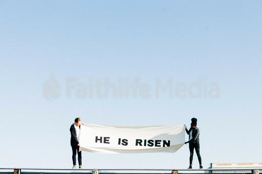 People Holding a He Is Risen Banner on a Rooftop