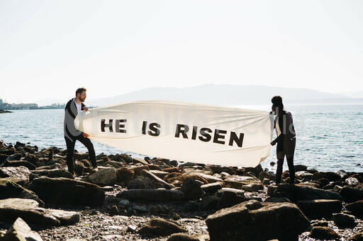 People Holding a He Is Risen Banner at the Beach