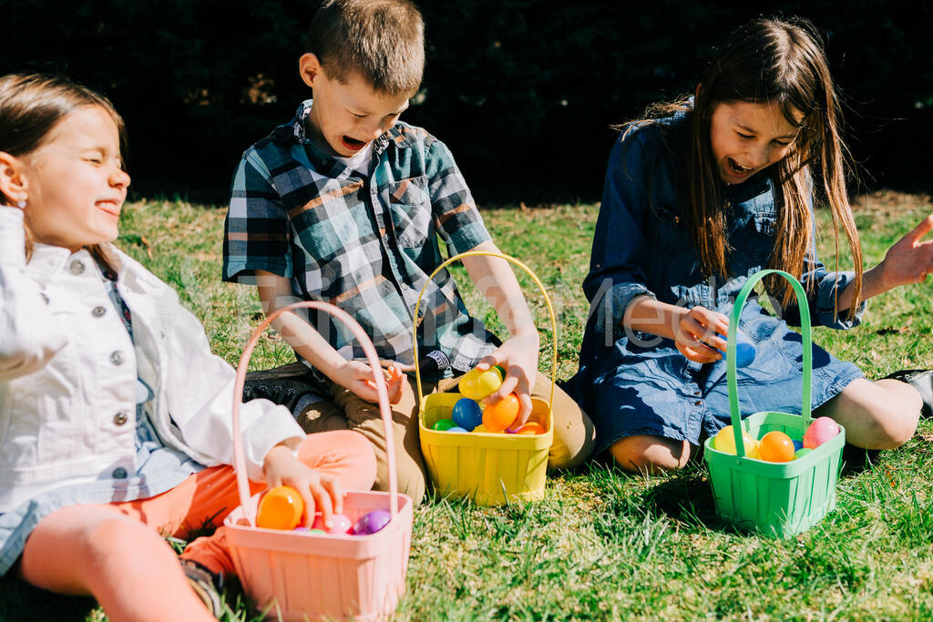Kids Laughing and Looking Through Their Easter Eggs Together large preview