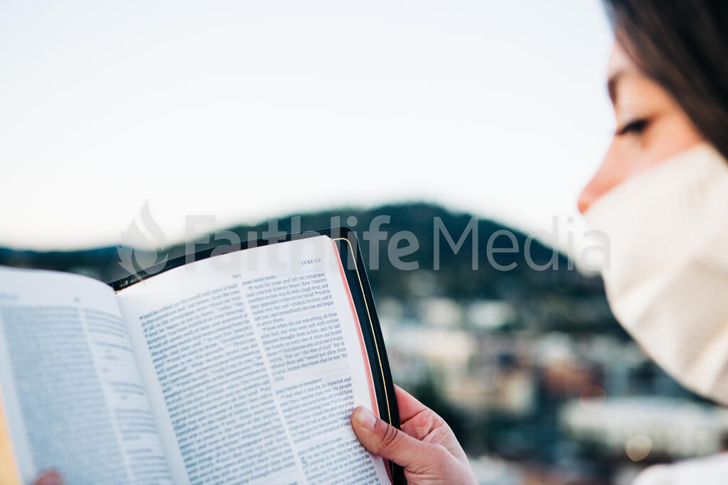 Woman Wearing a Face Mask and Reading the Bible large preview