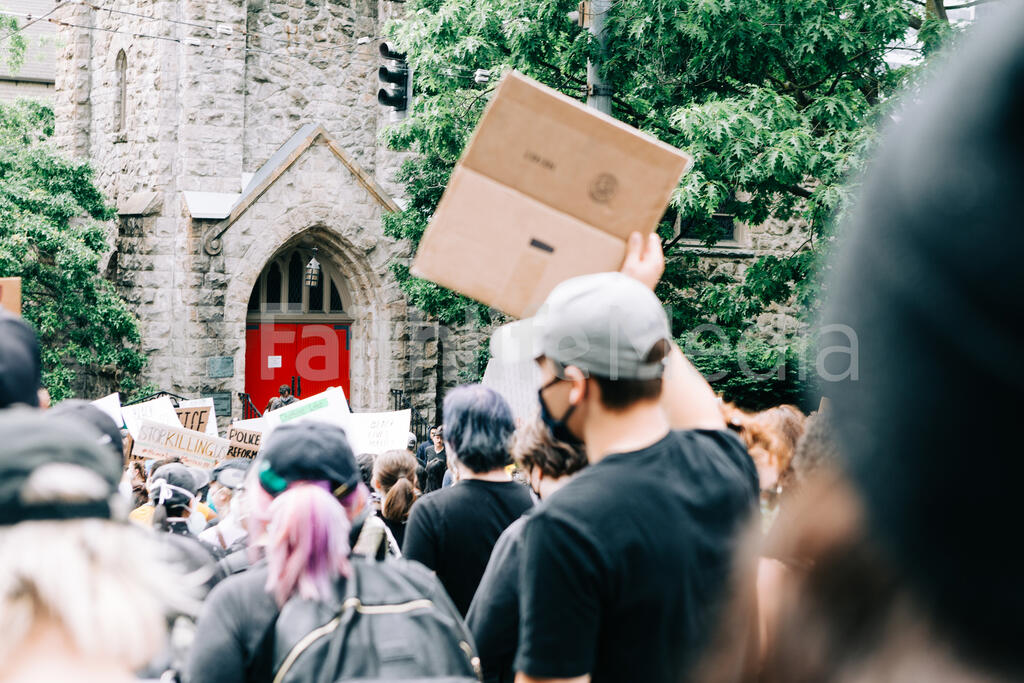 Peaceful Protesters Marching by a Church Building large preview