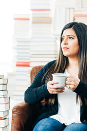 Woman Drinking Coffee Surrounded by Books  image 2