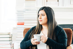 Woman Drinking Coffee Surrounded by Books  image 1