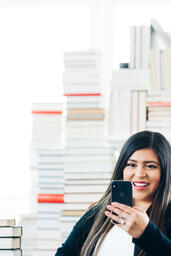 A Woman Studying on an iPhone in a Living Room Full of Books  image 10