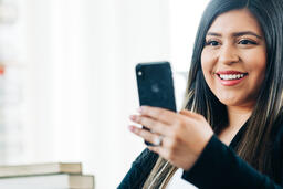 A Woman Studying on an iPhone in a Living Room Full of Books  image 11