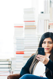 A Woman Studying on an iPhone in a Living Room Full of Books  image 1