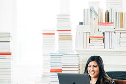 Woman Studying on a Laptop in a Living Room Full of Books  image 6