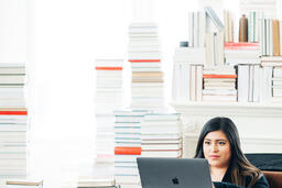 Woman Studying on a Laptop in a Living Room Full of Books  image 4