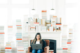 Woman Studying on a Laptop in a Living Room Full of Books.  image 3