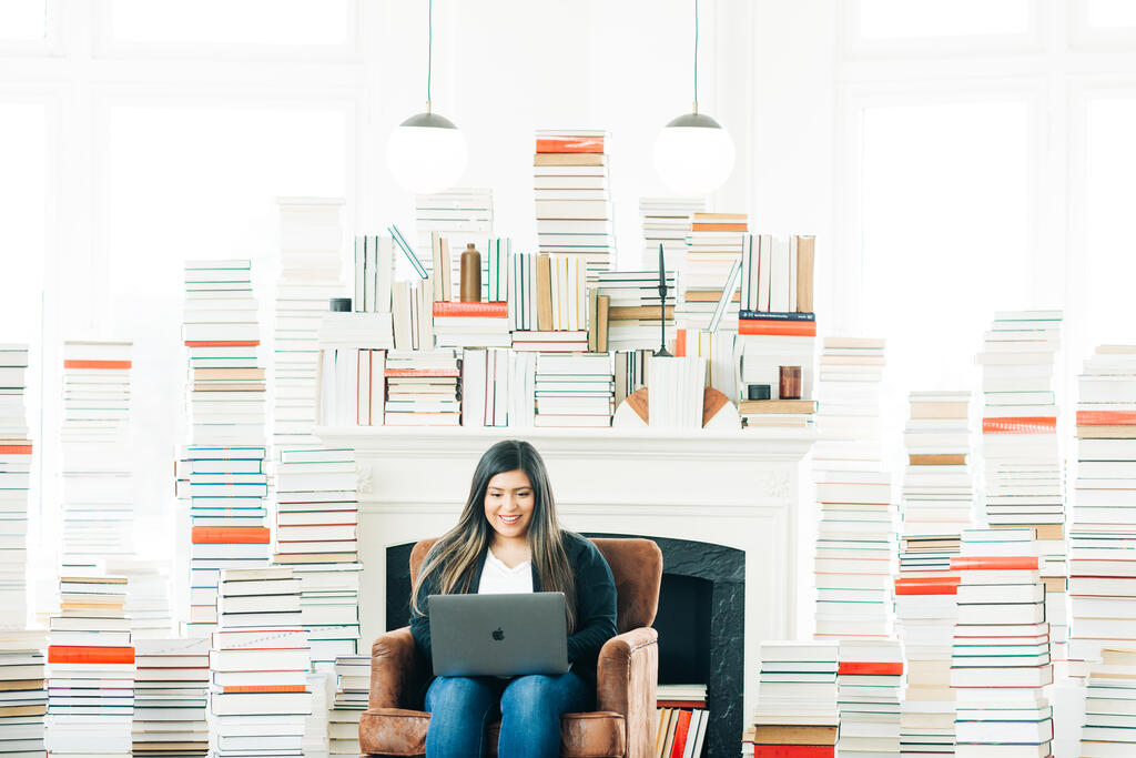 Woman Studying on a Laptop in a Living Room Full of Books. large preview