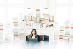 Woman Studying on a Laptop in a Living Room Full of Books.  image 2
