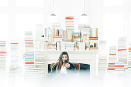 A Woman Studying on an iPhone in a Living Room Full of Books  image 2
