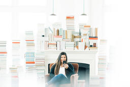 A Woman Studying on an iPhone in a Living Room Full of Books  image 3