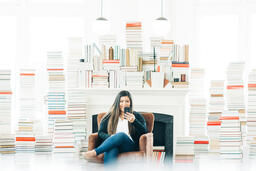 A Woman Studying on an iPhone in a Living Room Full of Books  image 4