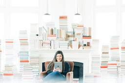 A Woman Studying on an iPad in a Living Room Full of Books  image 1