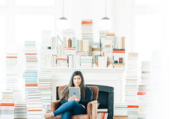 A Woman Studying on an iPad in a Living Room Full of Books  image 6