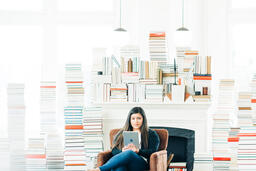 A Woman Studying on an iPad in a Living Room Full of Books  image 2