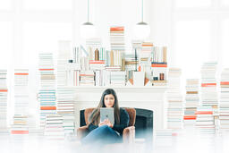 A Woman Studying on an iPad in a Living Room Full of Books  image 4