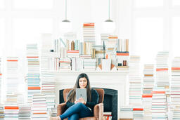 A Woman Studying on an iPad in a Living Room Full of Books  image 5