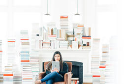 A Woman Studying on an iPad in a Living Room Full of Books  image 3