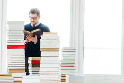 Man Reading a Book in a Living Room Full of Books  image 2