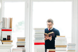 Man Reading a Book in a Living Room Full of Books  image 1