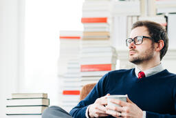 Man Drinking Coffee in a Room Full of Books  image 1