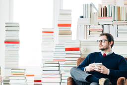 Man Drinking Coffee in a Room Full of Books  image 4