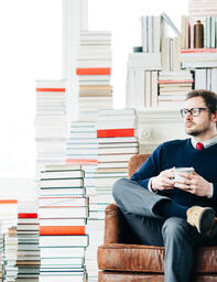 Man Drinking Coffee in a Room Full of Books  image 3
