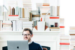 Man Studying on a Laptop in a Living Room Full of Books  image 11