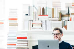 Man Studying on a Laptop in a Living Room Full of Books  image 13
