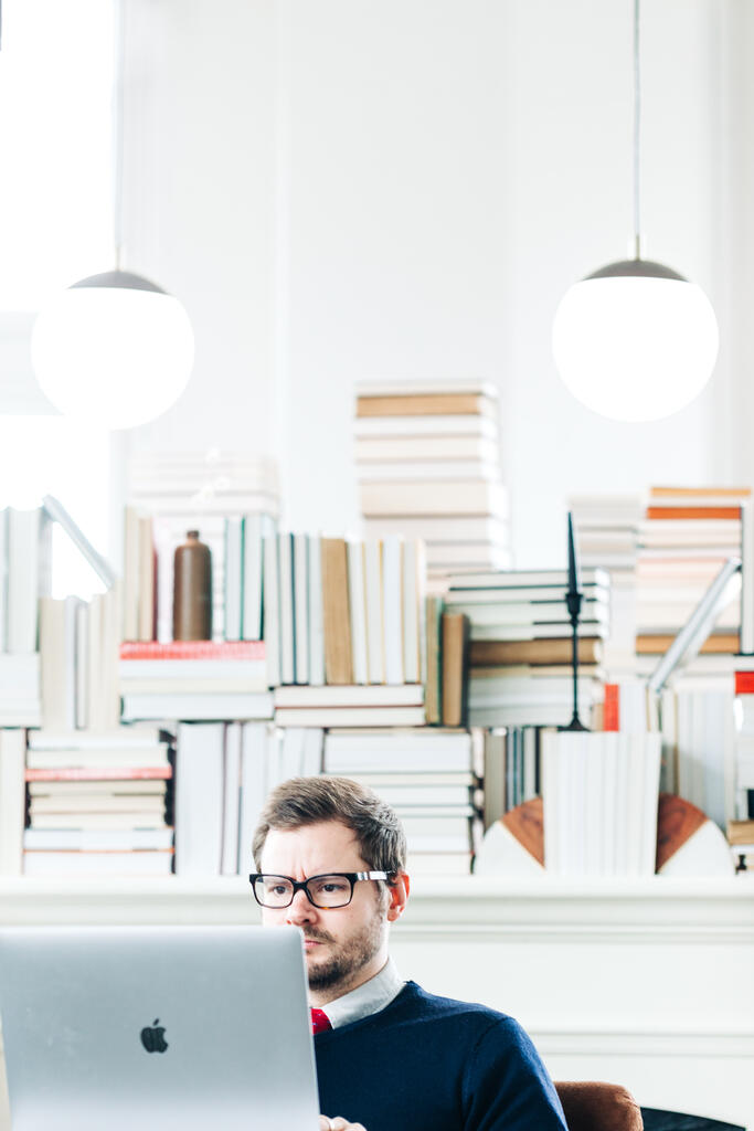 Man Studying on a Laptop in a Living Room Full of Books large preview