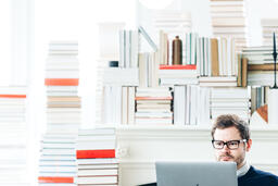 Man Studying on a Laptop in a Living Room Full of Books  image 10