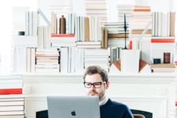 Man Studying on a Laptop in a Living Room Full of Books  image 5