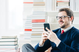 Man Studying on an iPhone in a Living Room Full of Books  image 1