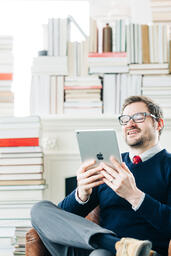 Man Studying on an iPad in a Living Room Full of Books  image 4
