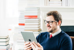 Man Studying on an iPad in a Living Room Full of Books  image 1