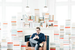 Man Studying on an iPhone in a Living Room Full of Books  image 2