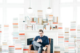 Man Studying on an iPhone in a Living Room Full of Books  image 4