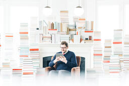 Man Studying on an iPad in a Living Room Full of Books  image 2